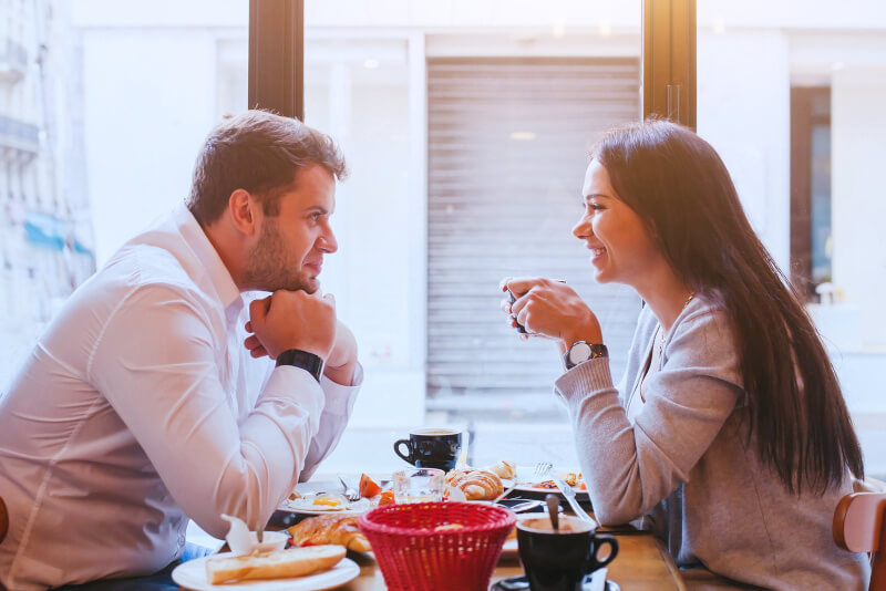 dating, man and woman laughing together in restaurant, happy couple drinking coffee and eating breakfast